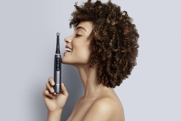Oral B Woman Holding iO Series Electric Toothbrush