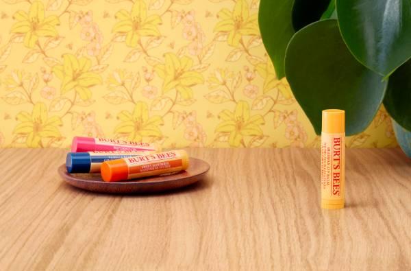 Burt's Bees Beeswax Lip Balm, Vanilla Lip Balm, Sweet Mandarin Lip Balm and Watermelon Lip Balm on a table