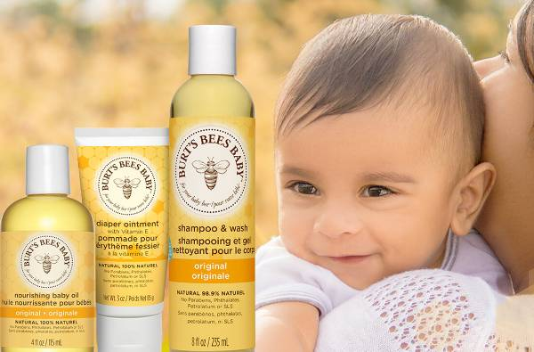 A mother holding her baby next to Burt's Bees Nourishing Baby Oil, Diaper Ointment and Baby Shampoo
