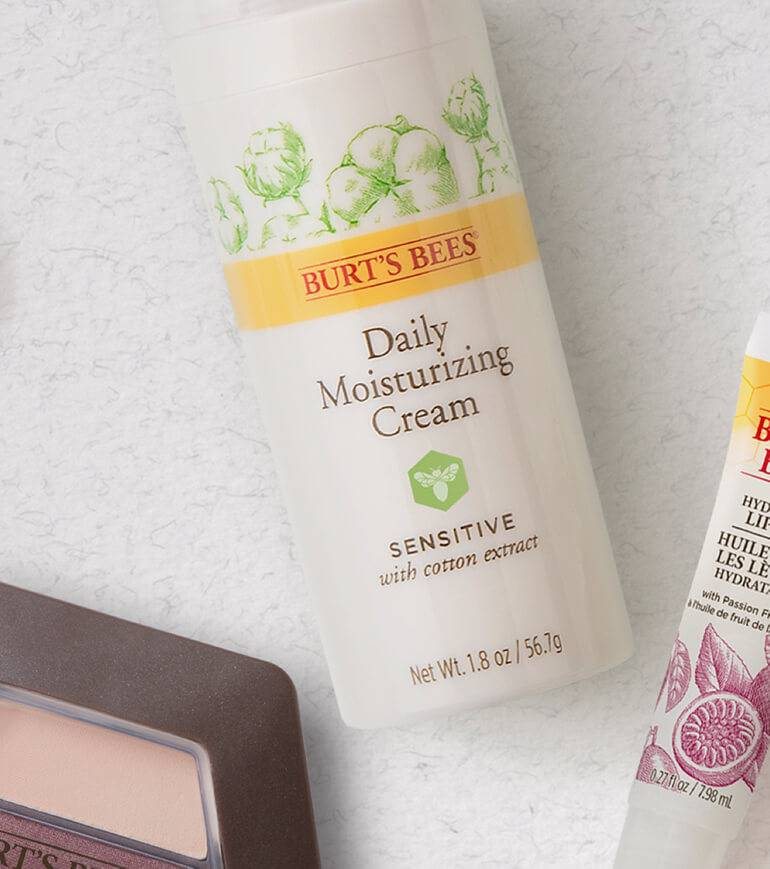 Burt's Bees products with recyclable packaging on a white background, including a lip balm, an eyeshadow trio & daily moisturising cream