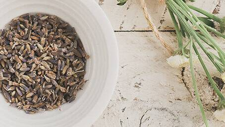 A bowl full of natural seeds & nuts next to a bunch of white flowers