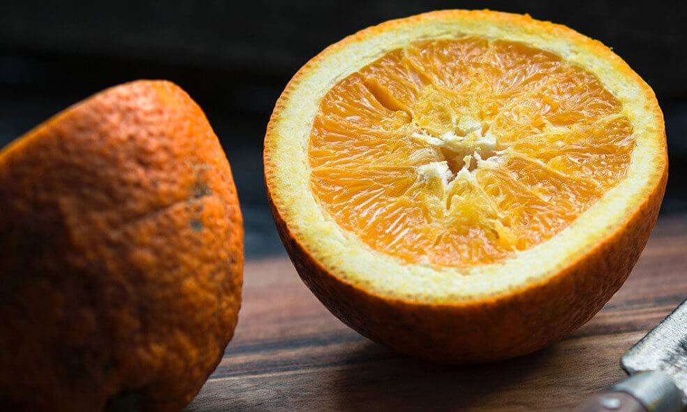 An orange sliced up into two halves on top of a wooden table