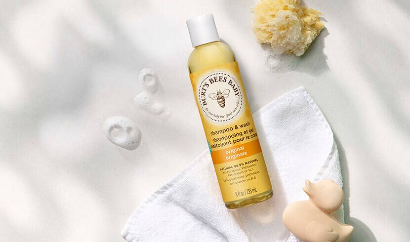 A bottle of Burt's Bees Baby Shampoo & Wash next to bubbles