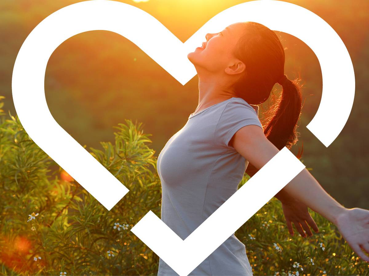 Individual smiling and posing in front of a sunset backdrop with a heart logo outline