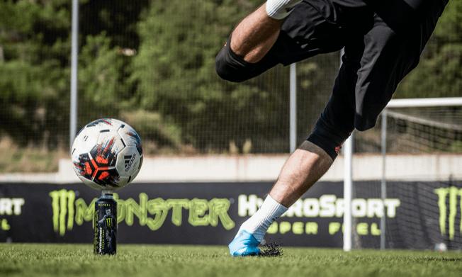 Man kicking a football balanced on top of a Monster HydroSport Bottle