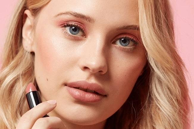 Model applying neutral tone lipstick