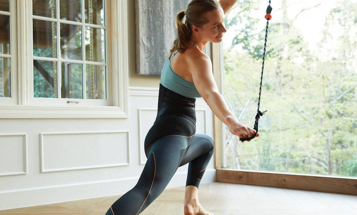 Woman stretching out legs whilst using sixpad ab belt