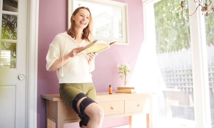 Woman standing up smiling, reading a book whilst using the Sixpad Leg Belt