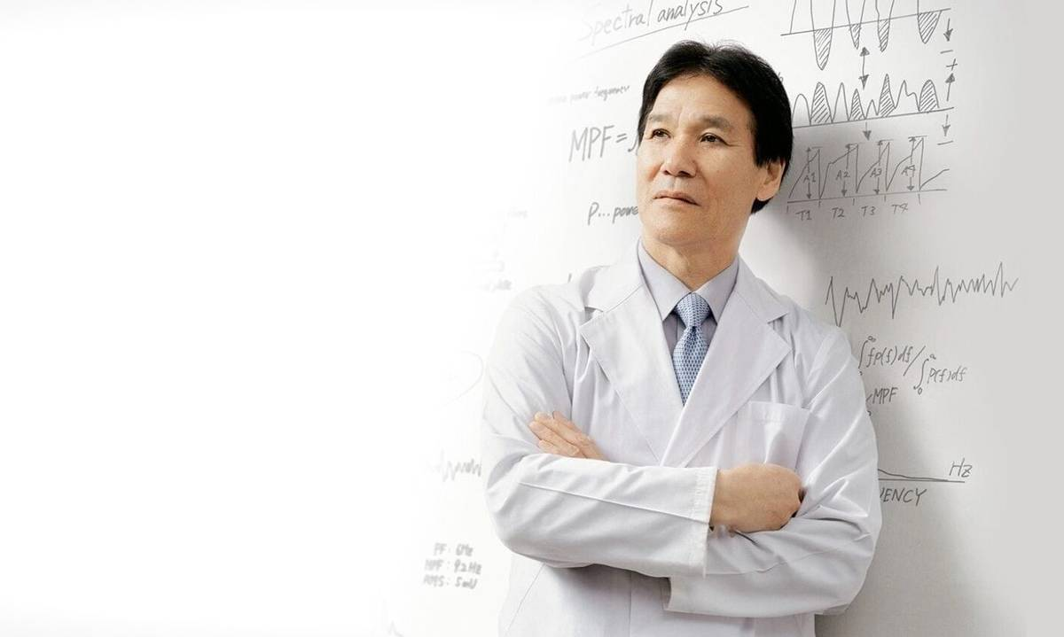 How Sixpad Works Toshio Moritani. Wearing a doctors uniform with EMS science on the board behind