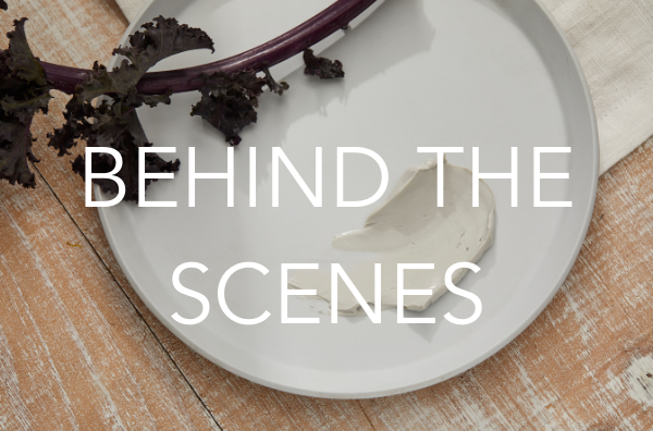 Behind the scenes text image on background with plate and a swatch of a masque and kale leaf for decoration.