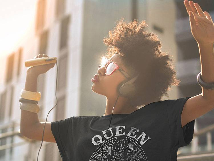 Woman dancing outside with her walkman in a Queen t-shirt