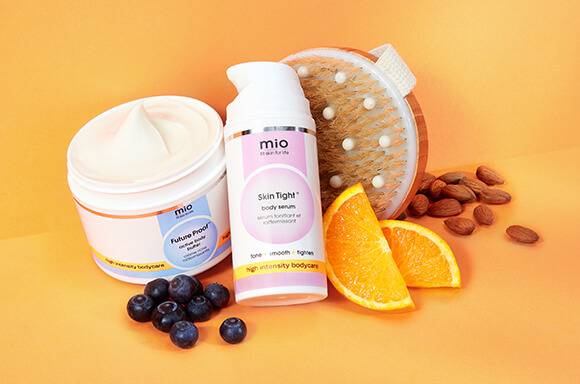 Image featuring three products against light orange backdrop displayed with orange slices, a handful of pomegranate seeds, and aloe leaves