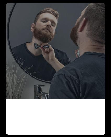 Bearded man shaving neck with King C. Gillette razor