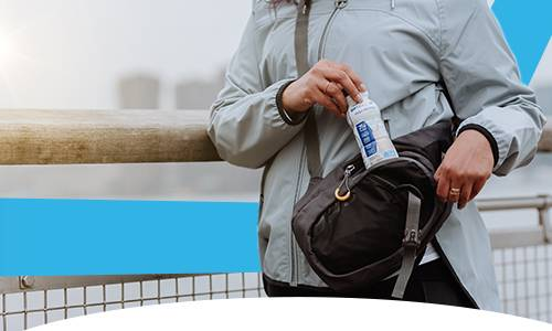 Image of a person putting an OPTIFAST drink into a bag