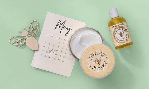 An open tub of Burt's Bees Mama Bee Belly Butter and Nourishing Body Oil on top of a calendar with a due date marked on it