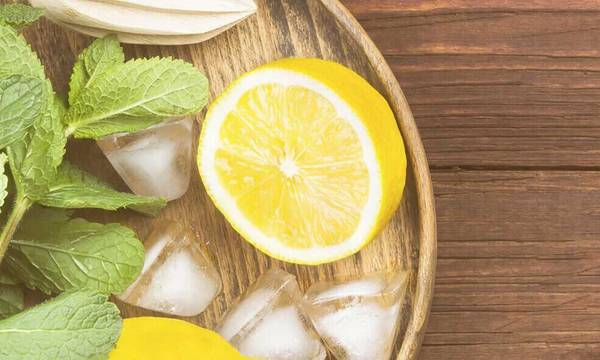 Half a lemon on a wooden tray next to mint leaves and ice cubes