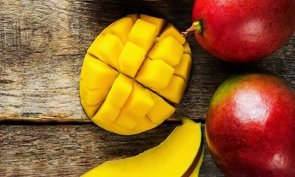 A sliced up mango next to whole mangoes