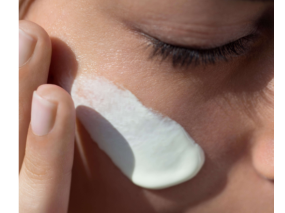 Lady applying nuxe cream to her face