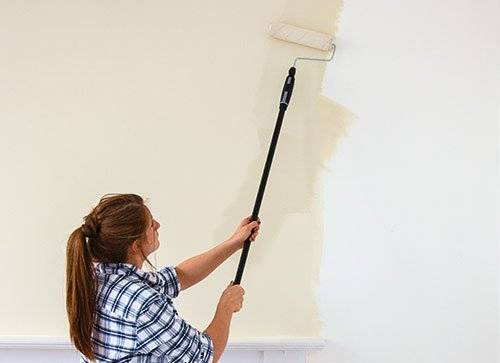 Woman painting the walls from white to beige