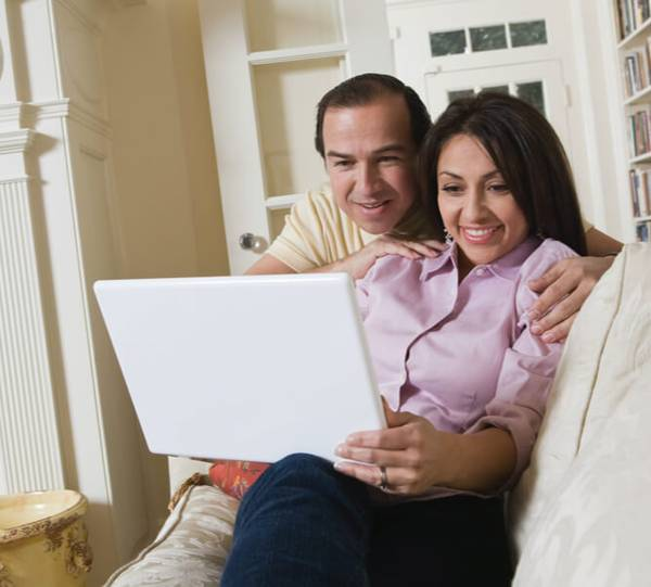 Couple looking at a white laptop