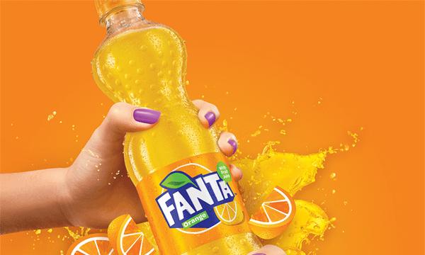 Bottle of Fanta surrounded by slices of orange