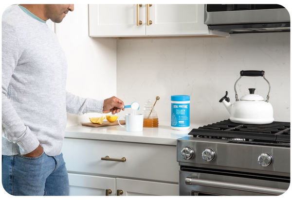 Vital Proteins collagen peptides on kitchen top with a women in the background drinking coffee