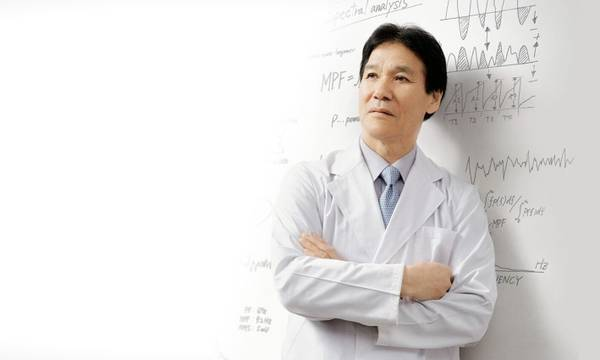Doctor in white uniform with equations on whiteboard behind