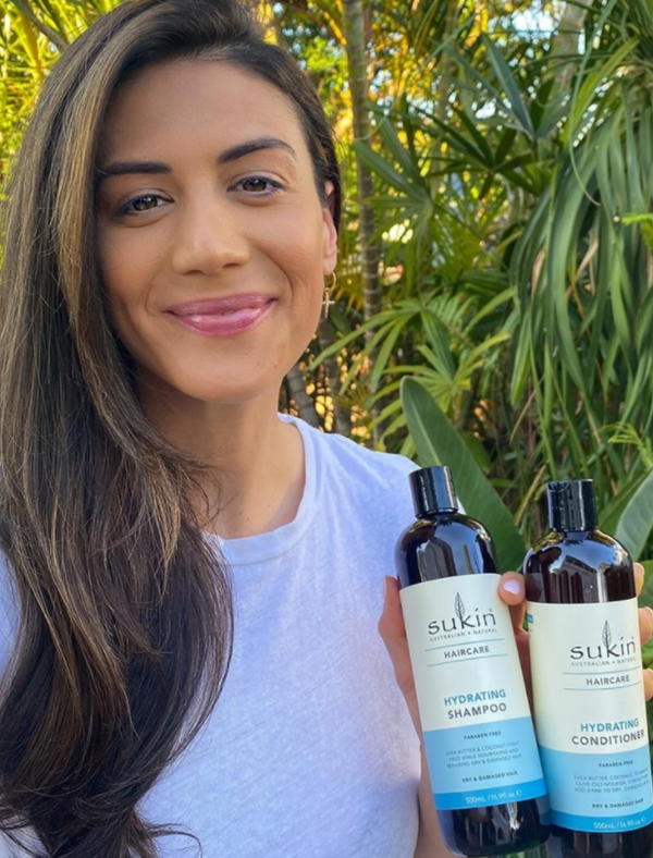 Girl on left side of image with nourished looking healthy hair and on the right she is holding the hydrating shampoo and conditioner. Visit @SukinSkincare Instagram