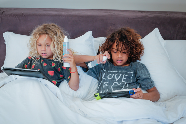 two children on a bed playing with their iPad and holding a spectrimist bottle. Visit our instagram