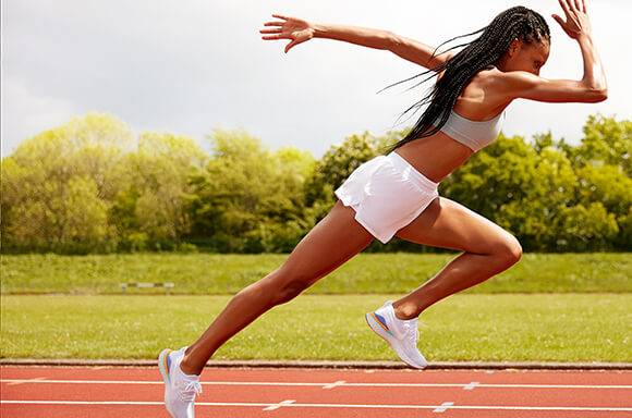 woman sprinting on running track